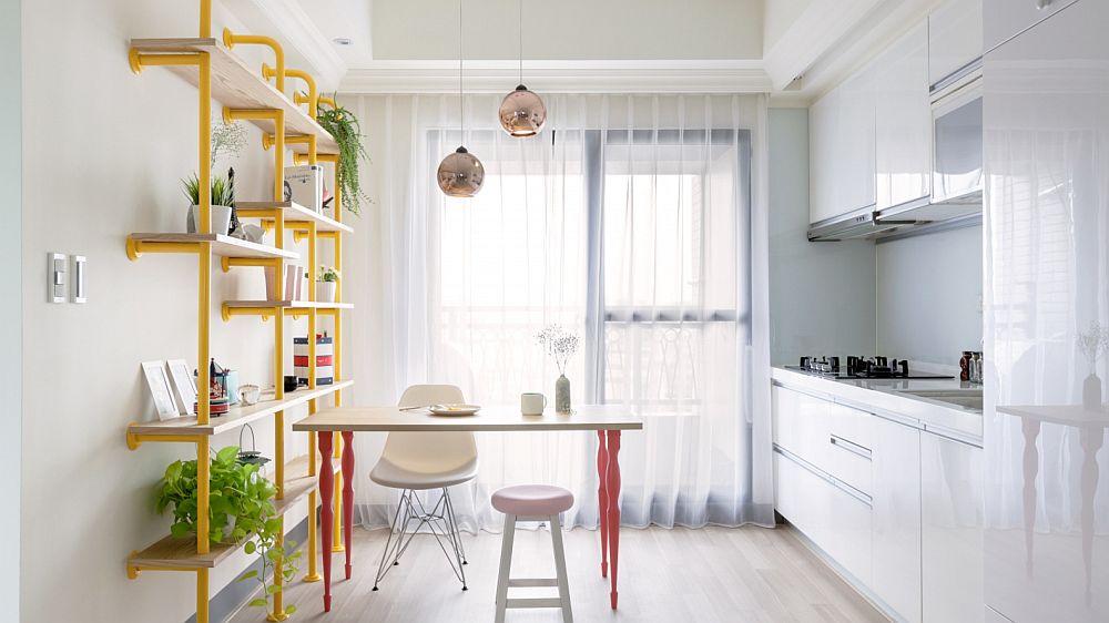 Prezența bibliotecii realizată din șevi vopsite în galben atrage atenția, la fel și picioarele mesei din zona bucătărie. Astfel, toată partea tehnică a bucătăriei, situată pe partea opusă, este oarecum discretă. Bucătăria este ca un volum alb pe un fundal alb. Designerii nici nu au dorit să atragă atenția asupra prezenței ei.