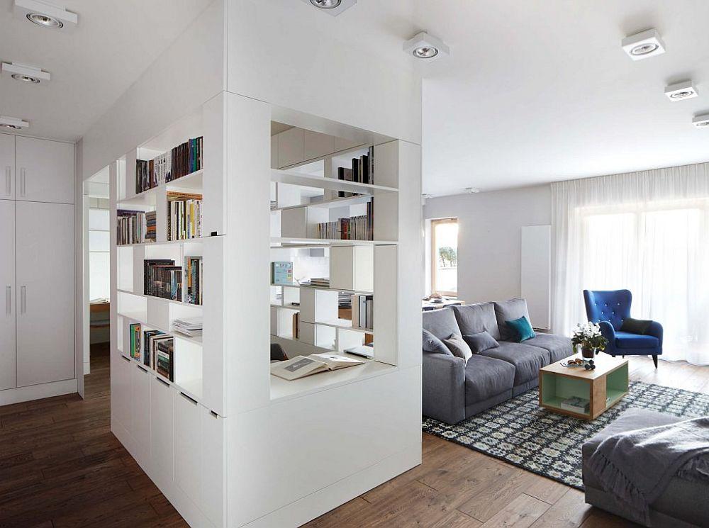 Între holul de la intrare și livingul deschis către bucătărie s-au desființat pereții. În acest loc arhitectele au prevăzut o bibliotecă sub forma unui paralelipiped, la interiorul căreia este un loc de birou. E adevărat că masa de birou este pentru lucrul la laptop, dar partea frumoasă este că nu-ți dai seama din prima că acolo ar exista o altă funcțiune. Totul arată ca și cum ar fi o bibliotecă mai interesantă.