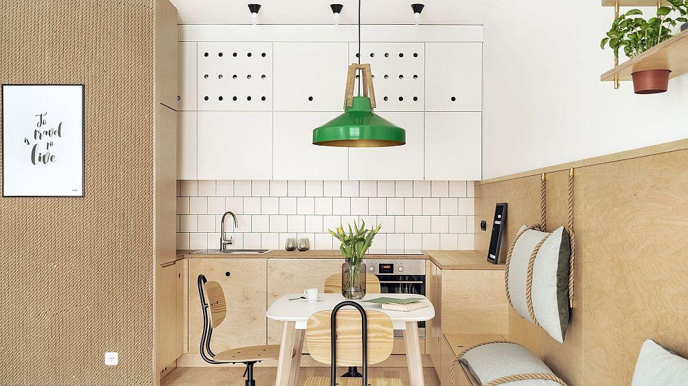 Bucătăria este minimală, dar bine organizată. Corpurile inferioare au fronturile din placaj, iar mânerele sunt configurate ca orificii în suprafața acestora. Hota, frigiderul, plita, cuptorul sunt încorporabile. În partea de sus, corpurile suspendate sunt configurate până în plafon, iar fețele albe perforate sunt ca motive decorative subtile în ambient.