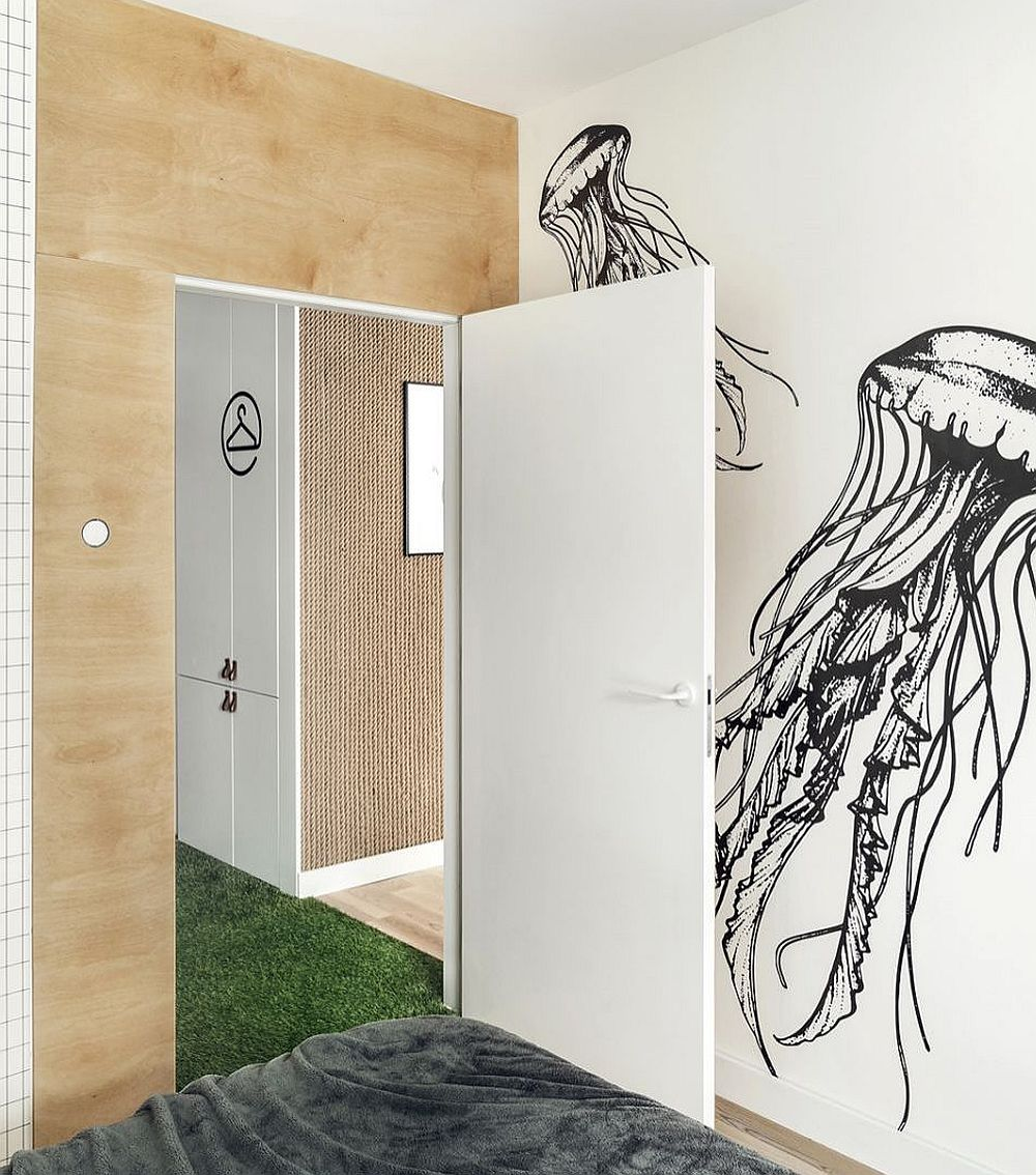 Accesul în dormitor este marcat prin placarea ușii și a zonei de ușă cu placaj din lemn. Chiar dacă pe o parte ușa este albă, odată închisă ea pare integrată în ansamblul cu lemn. Pe peretele din fața patului stickerele cu animale marine continuă tema amenajării.