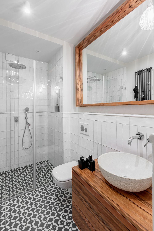 Baia de serviciu este simplă, dar de efect prin prezența elementelor din lemn - rama oglinzii și mobilierul pentru lavoar. Albul și negrul sunt o rețetă sigură pentru orice baie pentru că într-un asemenea context o mobilă diferită schimbă ambianța.