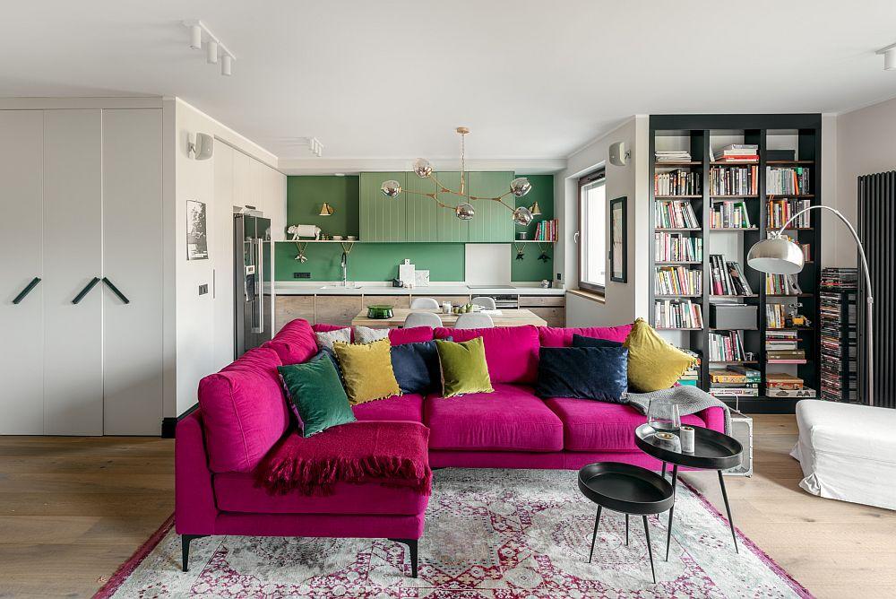 Ceea ce atrage din start atenția la intrarea în zona de zi este canapeaua cu o tapițerie într-o culoare îndrăzneață, dar această culoare nu ar fi fost percepută la fel dacă nu era în constrast cu pernele decorative și în relație cu nuanța complementară din zona bucătăriei. Combinația de roșu-verde este o schemă cromatică complementară, iar orice derivație a acestor nuanțe poate fi considerată la fel. Aici roz fucsia cu verde măr conferă o atmosferă veselă, tinerească, dă senzația de prospețime. Dar dincolod e culori contează și formele. Canapeaua are o alută elegantă imprimată și de picioare, care lasă lumina să evidențieze desenul covorului, deci nu încarcă spațiul, apoi bucătăria este ordonat și simplu concepută, fără corpuri masive, iar partea inferioară este cu textură din lemn pentru a da o tușă caldă ambientului. Albul este prezent la nivelul blatului, dar și la nivelul pereților, ceea ce face ca totul să fie mai luminos prin contrast, iar mobilierul negru - biblioteca, măsuțele par de-a dreptul desenate în context.
