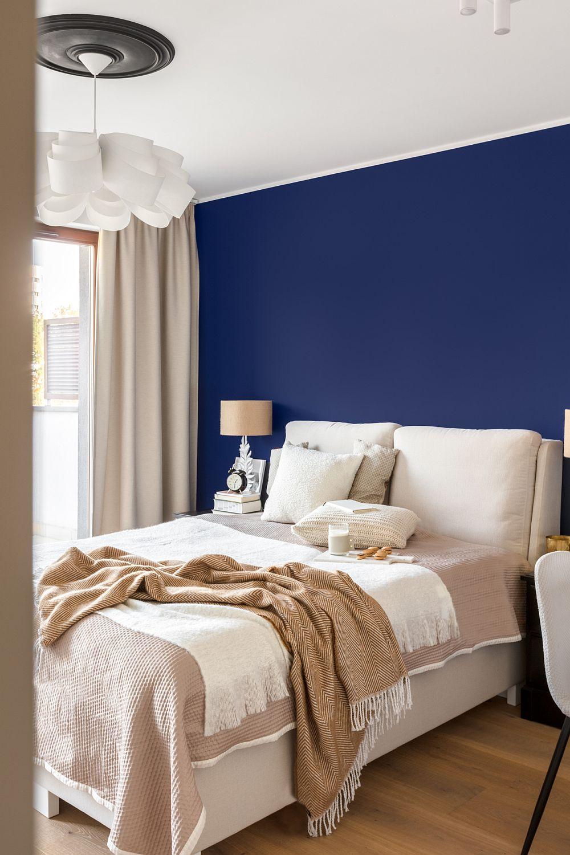 Dormitorul este simplu amenajat, dar are un aer elegant imprimat prin contrastul de culori, texturi și prin forma patului și a corpurilor de iluminat.