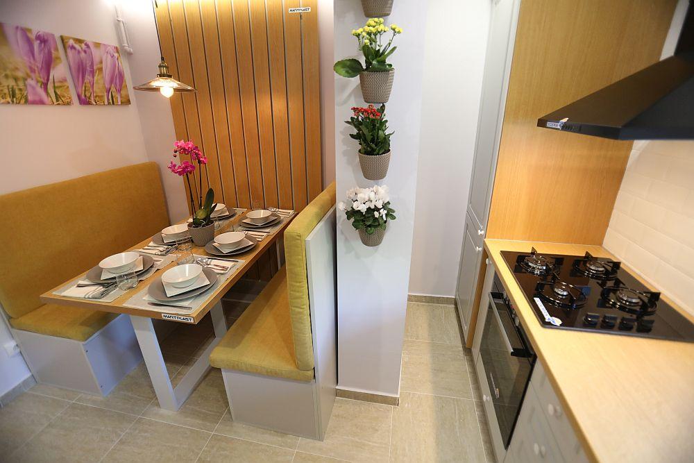 Chiar dacă spațiul este îngust, interiorul dulapurilor este accesibil. După peretele existent aici, în mobilier, este mascată centrala termică. Apoi urmează locul de plită și cuptor, electrocasnice alese de la sponsorul principal Dedeman.