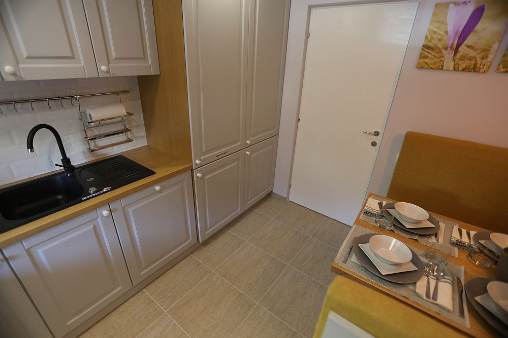 Sub chiuveta din bucătărie este loc pentru coșul de gunoi, dar este prezentă și o mașină de spălat vase încorporată în mobilier (acolo unde mînerul este așezat pe mijlocul ușii). Mai departe într-unul din corpurile înalte este mascat frigiderul încorporabil.