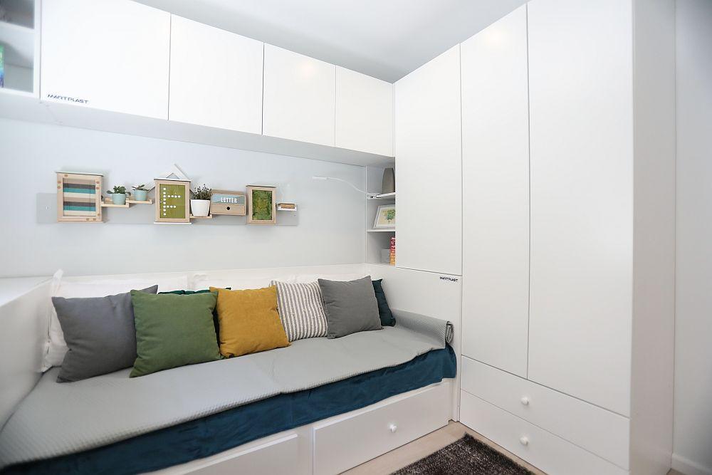 Desigur spațiile de depozitare nu lipsesc din camera lui Nicu. Pe lîngă dulapuri am prevăzut și corpuri suspendate. Rafturile libere sunt puține pentru ca aglomerarea de obiecte să fie împiedicată, însă sunt spații suficiente pentru organizarea lucrurilor. Totul pe alb pentru că încăperea este mică, iar Nicu este ordonat.
