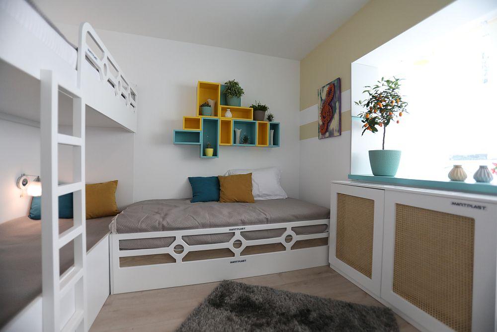 Al treilea pat este decorat diferit în partea din față, el putând fi folosit pe timpul zilei ca o mini canapea. Deasupra lui este un ansamblu de rafturi într-un contrast vesel galebn-turoaz. Toată mobila este realizată pe comandă la Martplast după proiectul Cristinei, iar decorațiunile, plantele, cuverturile și corpurile de iluminat sunt toate de la Dedeman.