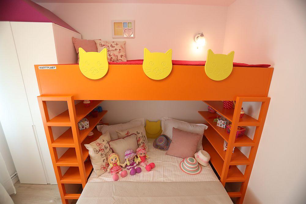 Accesul la patul de sus se poate face pe cele două șiruri de rafturi care încadrează patul de jos. Rafturile sunt prevăzute pentru depozitarea jucăriior. Pentru că fetițelor le plac animăluțele, și în special pisicile, Cristina a prevăzut ca în locul unei grilaj de protecție să existe un mini parapet cu figuri de pisici. Toată mobila este realizată ep comandă la Martplast, după proiectul Cristinei. Decorațiunile textile și corpurile de iluminat sunt de la Dedeman.