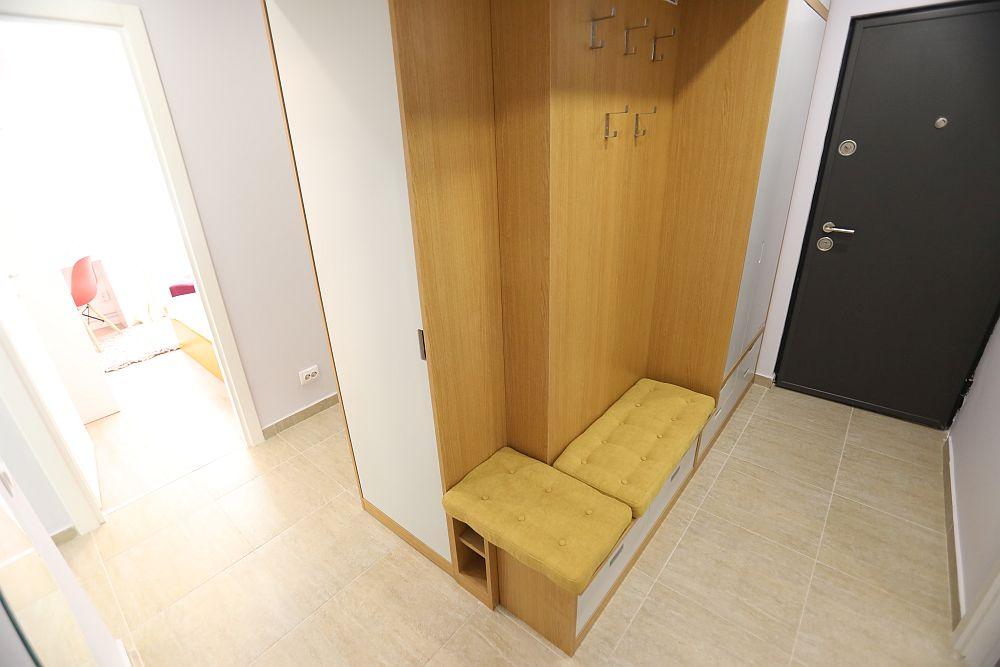 Holul de la intrarea în locuință a fost regândit cu loc de banchetă, cuier, iar spre ușă spațiu de depozitare închis pentru pantofi.