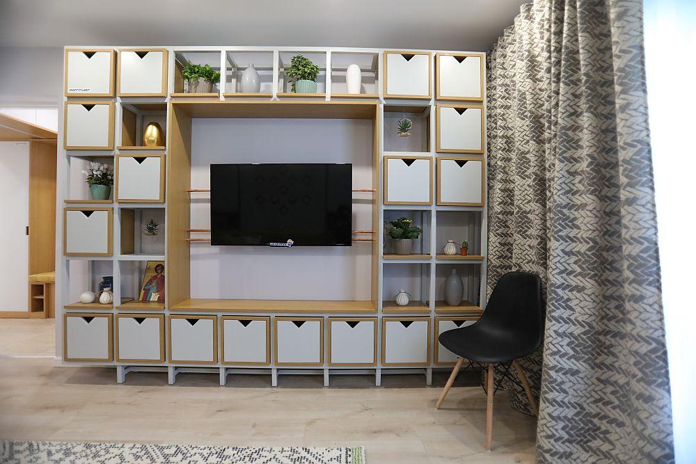 Biblioteca are multe cutii pentru depozitarea lucrurilor, astfel ca spațiile la vedere să fie cât mai puține și deci obiectele expuse să nu încarce ambientul camerei. Țevile din cupru ce susșin televizorul maschează și cablurile aferente acestui aparat electronic.