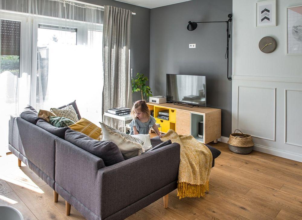 Zona de conversație și de tv este minimală, dar nici că ai avea nevoie de mai mult. Pentru ca ecranul televizorului să nu iasă în evidență, peretele din spatele lui a fost vopsit într-o nuanță de gri mai închis.