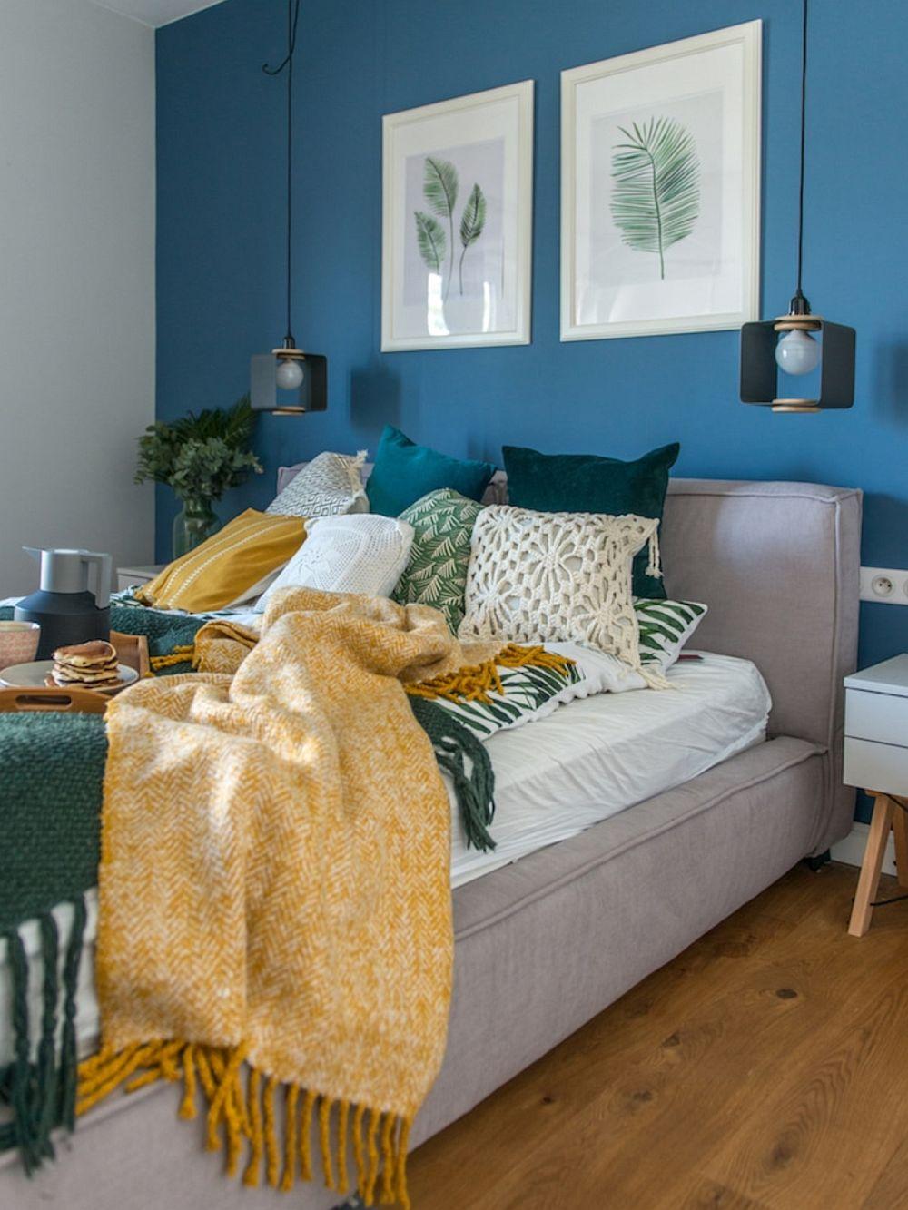 În decorul unei camere contează o nuanță de accent pe un perete, dar și mai mult contează modul cum este combinată cu restul obiectelor. Aici albastrul de pe perete devine odihnitor în relație cu tablourile cu paspartuu și rame albe și sugerează ideea de vacanță în relație cu decorațiunile textile de la nivelul patului.