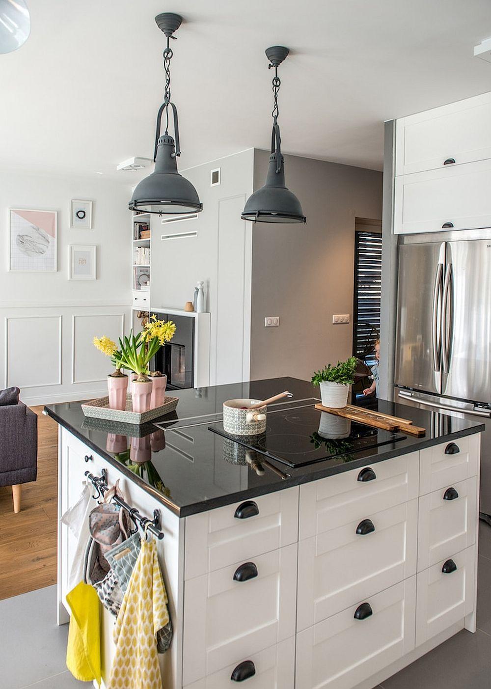 Bucătăria beneficiază de o masă de tip insulă, ca reper de delimitare între spațiul alocat altor activități decât gătitul. Tinerii și-au dorit un spațiu deschis la parter pentru a-și putea supraveghe fetița și pentru a petrece mai mult timp unii cu alții.