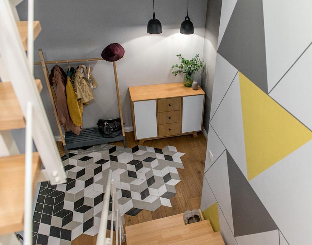 Din holul casei se face accesul la etaj prin intermediul unei scări interioare. Zona de intrare este vesel marcată prin placări ceramice jucăușe, iar peretele din zona scării este îmbrăcat cu un tapet realizat ep comandă.