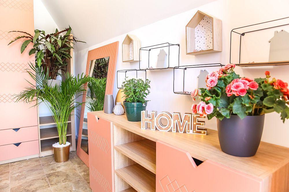 Față în față cu ușa de la intrarea în casă există un ansamblu de mobilier cu rol de cuier și pantofar. Mobila este realizată pe comandă la Martplast după proiectul lui Valentin Ionașcu. Plantele decorative și măștile de ghivece sunt de la Dedeman.