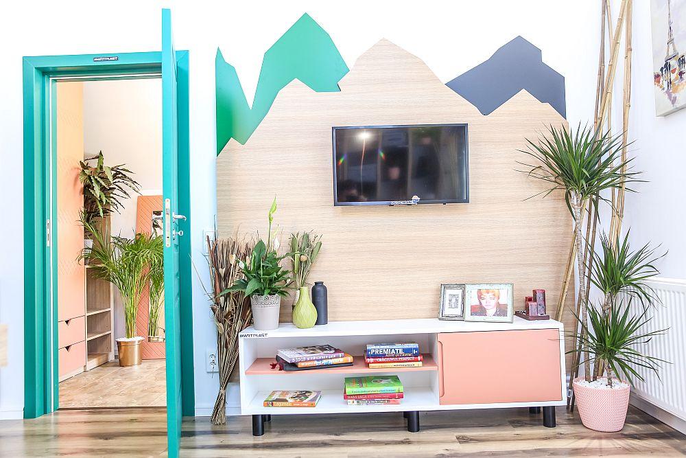 Din hol se accede în livin, care coexistă în același spațiu cu bucătăria. După ușa livingului se află locul de tv, masrcat de o placare decorativă prin care s-a dorit sugerarea unui peisaj de munte. Ușile interioare sunt realizate la Martplast, la fel și placarea și mobilierul. Televizorul, decorațiunile, plantele și parchetul sunt de la Dedeman.