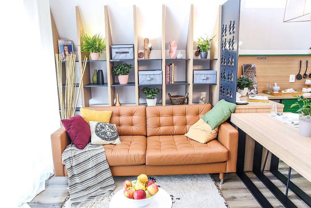 Livingul are un loc de conversație marcat prin prezența canapelei. În spatele acesteia este prevăzută o bibliotecă ce urmează panta casei. Canapeaua este de la Ikea, la fel și măsuța. Covorul, pernele decorative și obiectele decorative sunt de la Dedeman. Biblioteca este realizată pe comandă la Martplast după proiectul lui Ciprian Vlaicu.