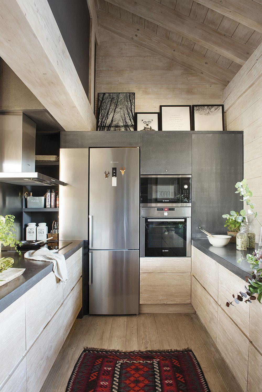 Bucătăria nu este mare, dar este excelent organizată în U. Partea de plită cu hotă este ascunsă prinvirii dinspre living, la fel și zona de frigider și alte electrocasnice încorporabile. Blaturile mobilierului sunt cu microciment, iar în jurul fridigerului și în spatele plitei pereții sunt placați cu foi de ardezie, o piatră care îmbrătrânește frumos. Totul în lemn și gri, dar covorul colorat este exact pata de culoare care trebuia.