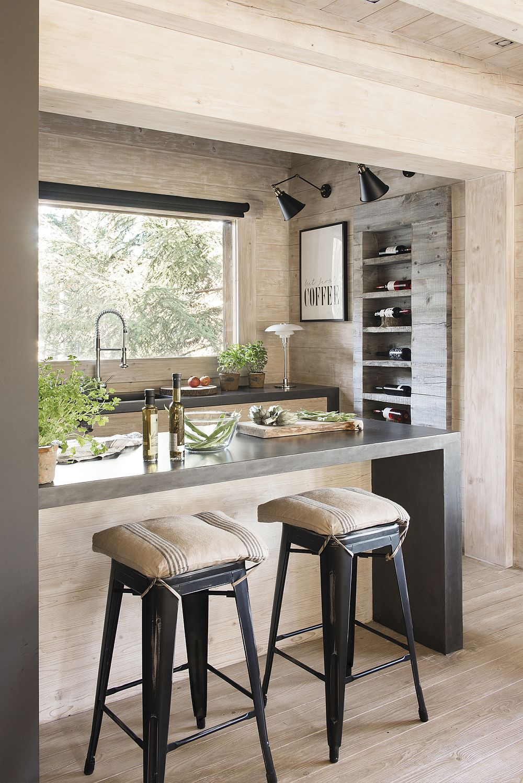 Bucătăria este amenajată ca într-o nișă marcată de un blat de masă de tip bar. Partea frumoasă este că la vedere sunt puține dotări, astfel încât aspectul general al parterului să nu fie alterat de electrocasnice.