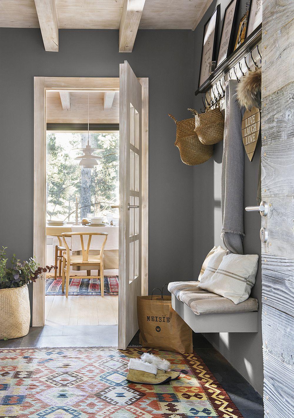 Intrarea în casă se face pe un mic hol, care vorbește despre stilul general al interiorului: simplu, contemporan, dar cald. Lemnul deschis la culoare este combinat cu zone de gri, iar decorațiunile textile, în special covoarele adaugă culoare interiorului.