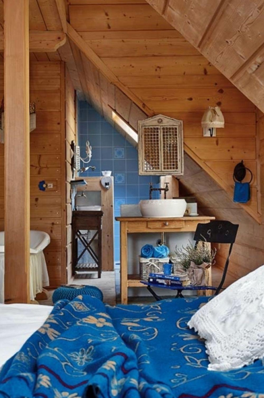 Unele dormitoare au baia configurată deschis către zona de odihnă. O soluție interesantă, dar și economică pentru că spațiul de sub pante a putut fi mai bine exploatat. De asemenea, necesarul de plăci ceramice a fost diminuat, lemnul râmânând dominant în încăpere.