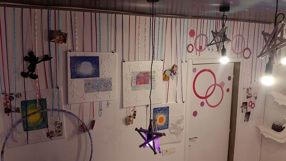 În fașa patului, pe peretele cu ușa i-am făcut Anastasiei o instalație jucăușă cu panglici colorate de care își poate prinde desenele sau alte lucruri dragi ei. Și ușa a fost incadrată în această instalație, lipind pe ea stickere decorative sub formă de cercuri.