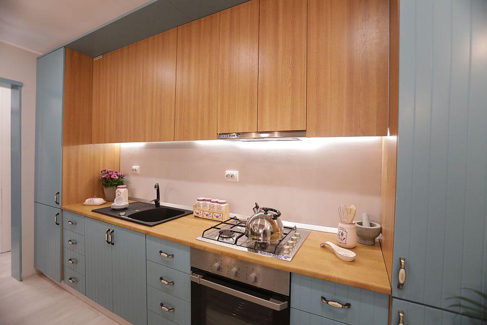 Toate electrocasnicele sunt încorporate, inclusiv hota și frigiderul, iar o bandă LED luminează zona de blat.