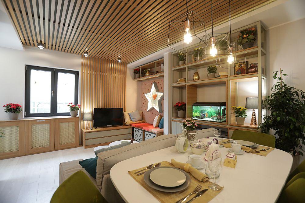 În saptele canapelei este așezată masa, la granița dintre living și bucătărie.