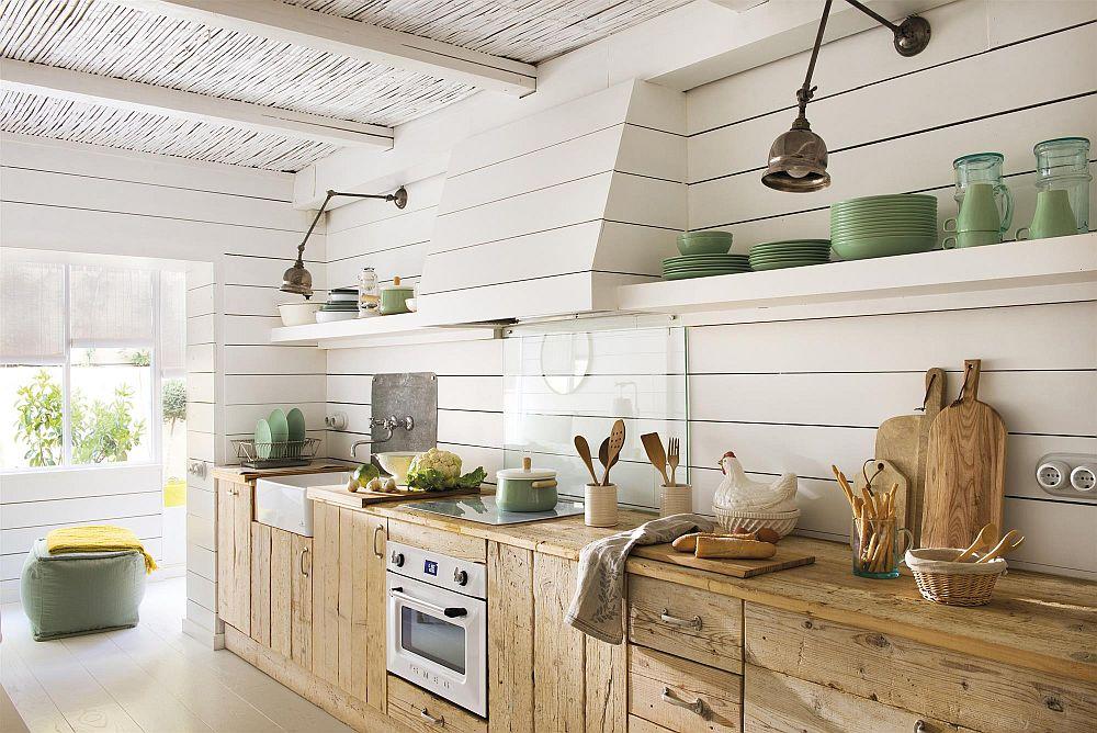 Bucătăria este interesant mobilată. În partea superioară hotal este îmbrăcată similar pereților, cu lambriuri și încadrată de rafturi, iar în partea inferioară mobilierul este realizat din lemn recuperat, care dă o notă rustică, dar actuală și caldă spațiului. Zona de foc, respectiv din dreptul plitei, este protejată cu un panou de sticlă securizată pentru a nu altera desenul lambriurilor.
