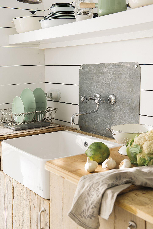 În zona de chiuvetă a bucătăriei peretele este placat doar cât e nevoie cu un panou metalic în acord cu bateriile care au un design vintage.