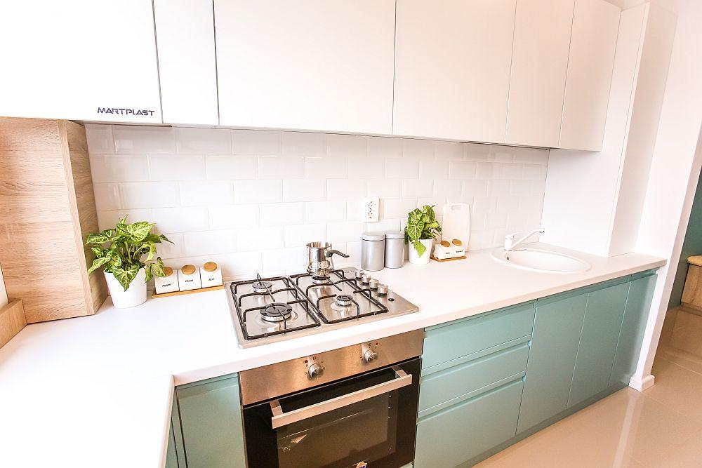 Bucătăria are fronturile din MDF vopsit, iar blatul alb pare să se continue cu faianța albă și corpurile suspendate. Totul simplu, ușor de curățat și ngrijit, dar și luminos și plăcut, mai ales că bucătăria nu este separată față de holul de la intrare, deci să se vadă armonios totul încă de la intrarea în locuință.