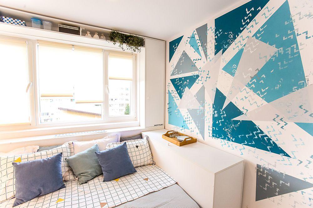 Am personalizat peretele din zona patului cu picturi direct pe perete, forme mai geometrice pentru a păstra aspectul ordonat al ambientului. Aceste desene realizate cu vopsea acrilică vin să ofere o pată de culoare în camera pe care am gândit-o pe alb, să fie cât mai luminoasă.