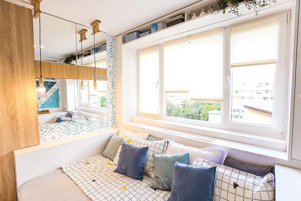 Pentru a amplifica spațiu mic al camerei, dar și pentru mai multă lumină naturală, la capătul patului am prevăzut o placere cu oglinzi. Corpurile de iluminat sunt de la Dedeman. Zonele de PAL cu textură de lemn vin să mai încălzească ambientul. M-am folosit și de spațiul de deasupra ferestrei pentru a configura acolo un raft pentru depozitare. Caloriferul este mascat. Toată mobila este realizată pe comandă la Martplast.