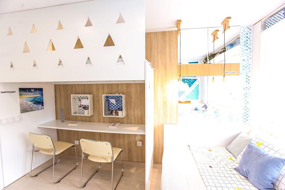 Placarea de lemn este continuată pe peretele unde este amplasat patul etajat și birourile pentru a proteja peretele, dar și pentru a asigura senzația de căldură.