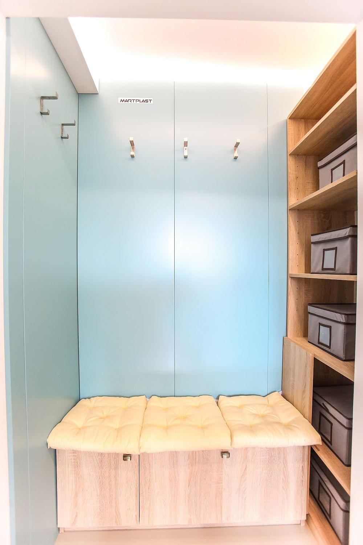 În nișa holului de la intrare am prevăzut o banchetă cu spațiii de depozitare, dar și un ansamblu cu rafturi pe verticală.