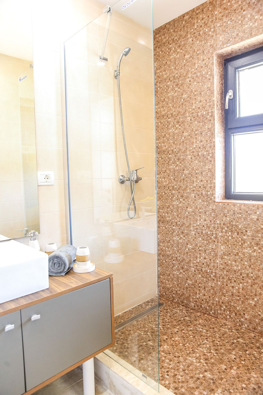 Pe partea opusă vasului de toaletă se află locul de duș, amenajat cu plăci ceramice și dotări de la Dedeman. Tâmplăria ferestrelor este asigurată în toată casa de Gealan, unul dintre sponsorii emisiunii.