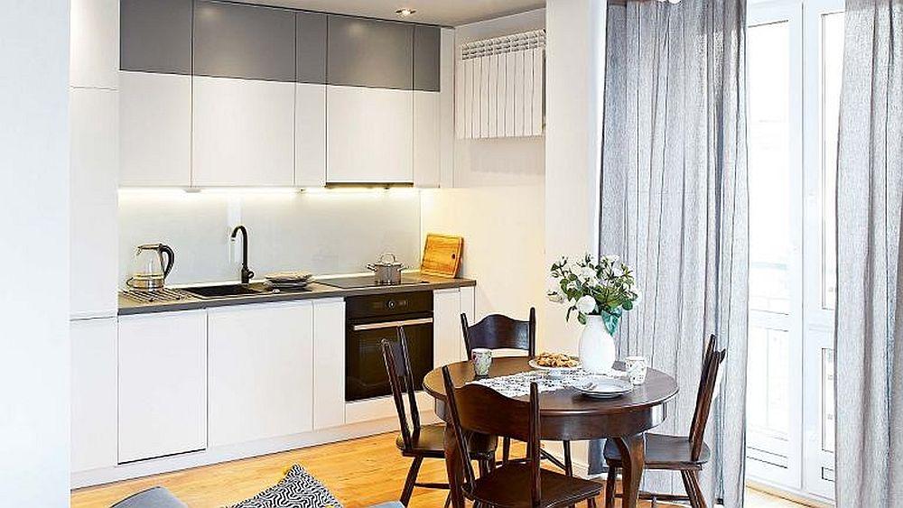 În spațiile mici orice centimetru pătrat contează, așa că se mai fac și compromisuri. În cazul de față caloriferul a fost montat la înălțime pentru ca el să nu incomodeze accesarea părții inferioare a corpurilor de mobilier din bucătărie. De asemenea, pentru a păstra imaginea cât mai ordonată a bucătăriei, arhitecții au avut în vedere un mobilier fără mânere, dotat cu sisteme push, ascunse. Partea de sus a corpurilor suspendate a fost vopsită într-o nuanță de gri pentru ca întreaga bucătărie să fie percepută la scară umană, deci mai joasă.