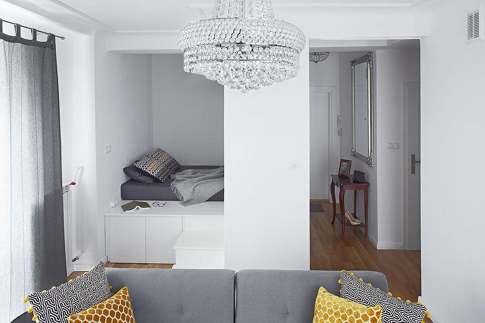 Intrarea în garsonieră se face pe un hol deschis către cameră, dar locul de dormit, vizibil din cameră este separat faă de hol cu panouri din PAL. O mică consolă cu o oglindă deasupra sugerează funcțiunea de hol de intrare.