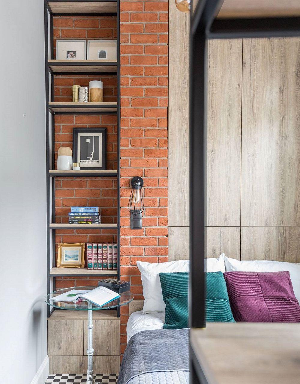 Partea cea mai vizibilă din dormitorul de lângă bucătărie este finisat cu cărămidă aparentă pentru o imagine unitară. Și nișa de aici a fost folosită pentru inserarea unei etajere metalice. Evident, toată mobila din garsonieră a fost realizată pe comandă.
