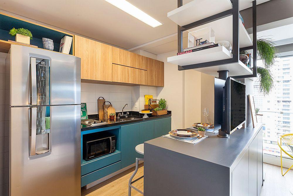 Bucătăria este grupată pe o singură latură, iar corpurile suspendate maschează hota, dar asigură și locuri de depozitare închise. Textura de lemn încălzește spațiul creionat în majoritatea suprafețelor în tonuri de alb și gri. Partea inferioară a bucătăriei este în aceeași nuanță ca și peretele lung al garsonierei, deci o legătură cromatică care se simte de la intrarea în garsonieră.