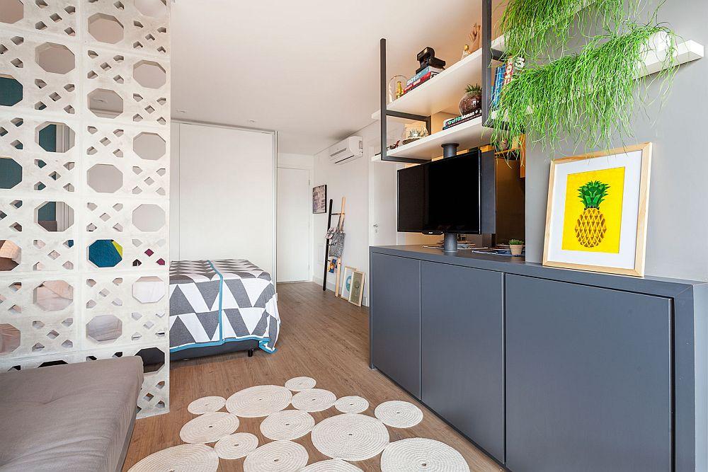 Intrarea în locuință coincide cu cea în spațiul deschis. În loc de hol, există un ansamblu de mobilier gândit în L care oferă loc de cuier imediat la intrarea în locuință, iar mai departe formează ansamblul de depozitare - un dulap generos cu uși albe.