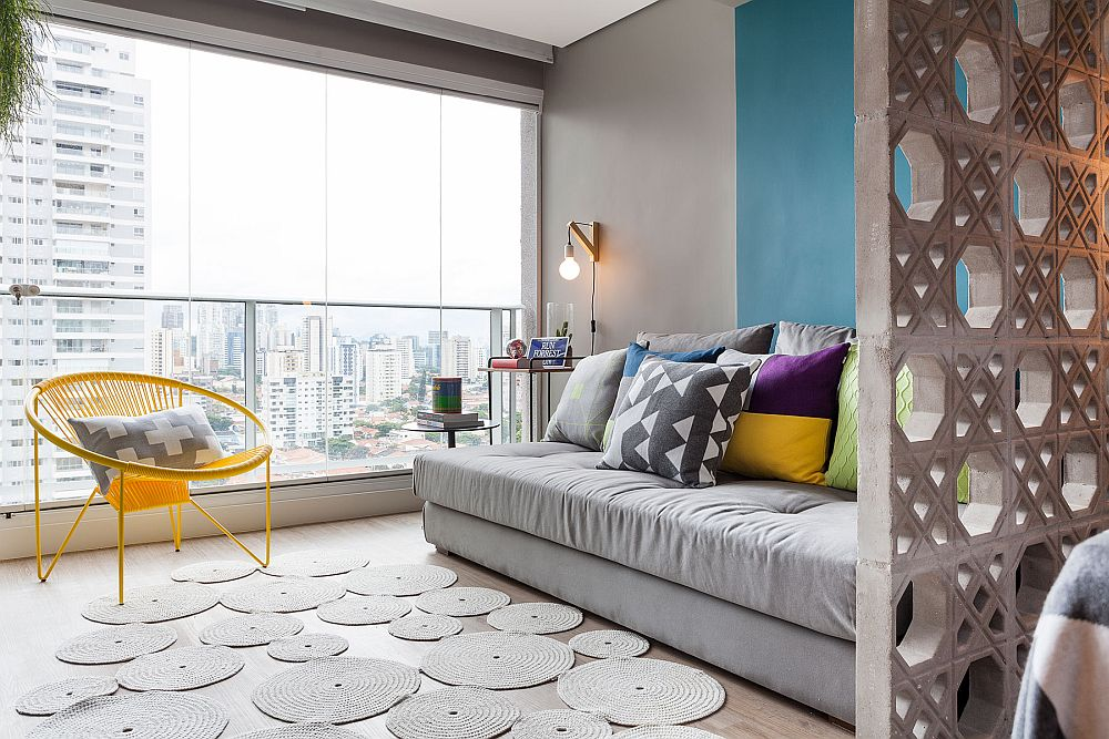 Spațiul extins al camerei către balcon a fost excelent exploatat pentru că a permis configurarea unui mini living care beneficiază de o fereastră generoasă. Deci, chiar dacă spațiul este mic el nu se simte claustrofobic. Un fotoliu în plus pe lîngă canapea nu strică niciodată. De reamarcat însă forma canapelei, una fără mânere. Este un mode extensibil pentru a asigura un loc în plus de dormit, atunci când este cazul.