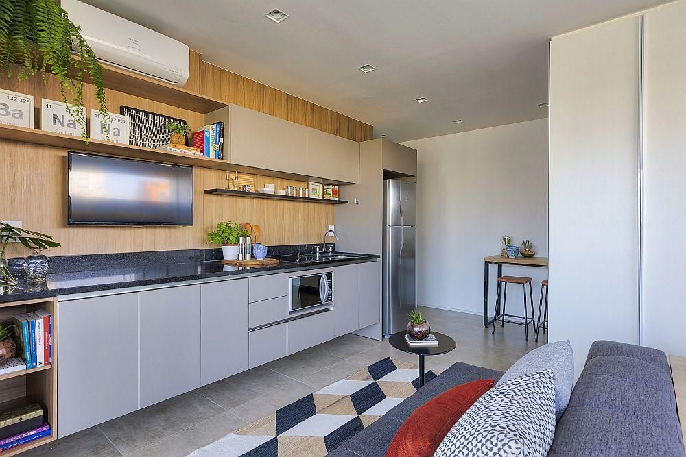 Bucătăria este configurată pe o singură latură, iar corpurile inferioare sunt suspendate pentru a lăsa la vedere mai mult din pardoseală. Este un truc care dă impresia de spațiul mai generos.