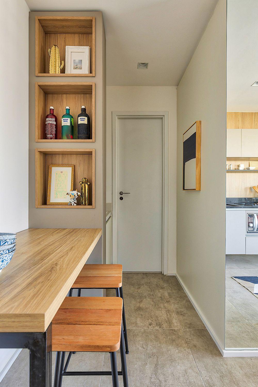 După cum se poate observa, zona de lavoar este mascată de o etajeră fixă cu nișe în prelungirea căreia se află masa cu scaunele de tip bar. Imediar după lavoar este ușa de intrare în baie, care include doar vasul de wc și un duș minimal.