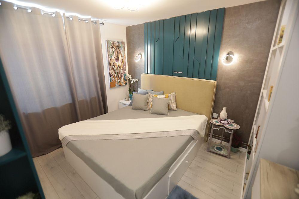 Dormitorul a fost amenajat conform proiectului Cristinei Joia, care a regândit poziționarea mobilierului față de ce era înainte. Astfel, acum patul este pe mijloc, dulapul în fața patului, iar biblioteca și masa de toaletă în dreapta. Mobila este realizată pe comandă la Martplast. Placarea de pe perete este realizată tot la Martplast din MDF vopsit, iar de o parte și de alta placării peretele este finisat cu tencuială decorativă de la Kober. Pe post de noptieră este o piesă a familiei repictată de către Cristina. Corpurile de iluminat, decorațiunile textile, draperiile sunt de la Dedeman.