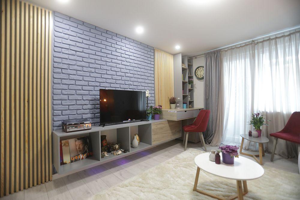Pe partea opusă canapelei, Valetin a prevăzut locul comodei pentru televizor și un loc de birou cu bibliotecă. Mobila este realizată pe comandă la sponsorul Martplast. Pe perete sunt rifleje din lemn realizate pe comandă la Martplast. Cărămida decorativă este de la Dedeman și a fost vopsită cu vopsea lavabilă într-o nuanță bleu. Sub comodă sunt lumini LED prevăzute conform proiectului lui Valentin.