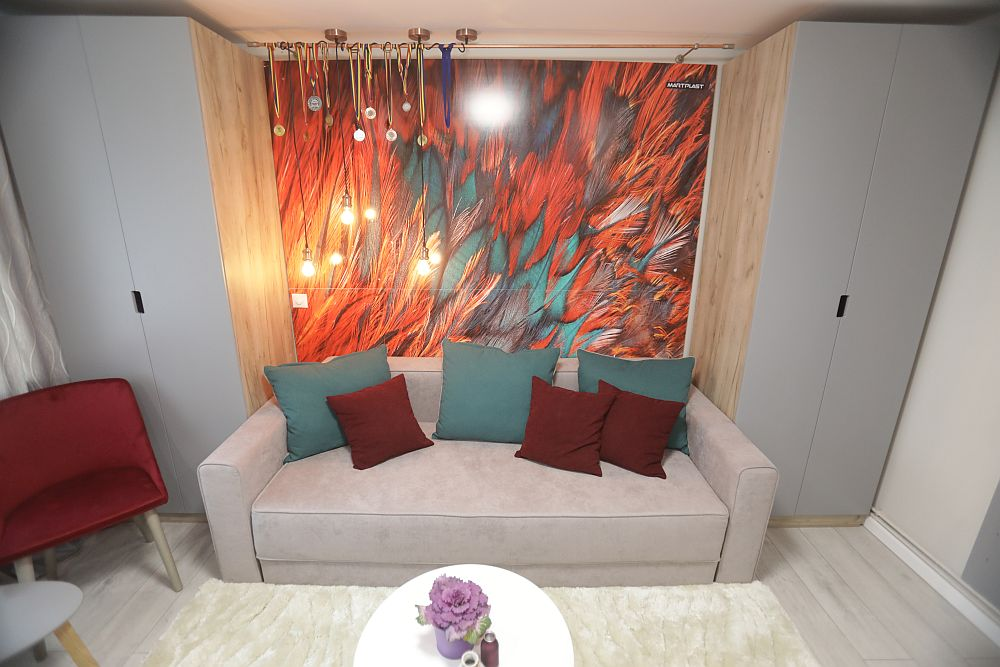 Deasupra canapelei peretele este placat cu PAL imprimat cu o imagine supradimensionată cu pene colorate, conform indicațiilor lui Valentin. Deasupra placării, la nivelul tavanului este o galerie de perdele folosită pentru expunerea medaliilor. De o parte și de alta a canapelei sunt dulapuri pentru depozitarea lucrurilor fetelor.