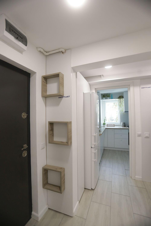 Holul locuinței este mic, dar în spațiul lui a fost acomodat frigiderul, acesta nemaiavând loc în spațiul mic al bucătăriei, unde familia și-a dorit să păstreze un loc de luat masa. Peretele din dreptul ușii este placat cu PAL alb peste care s-au aplicat trei rafturi pătrate, loc pentru lucruri mici, care se doresc a fi la îndemână.