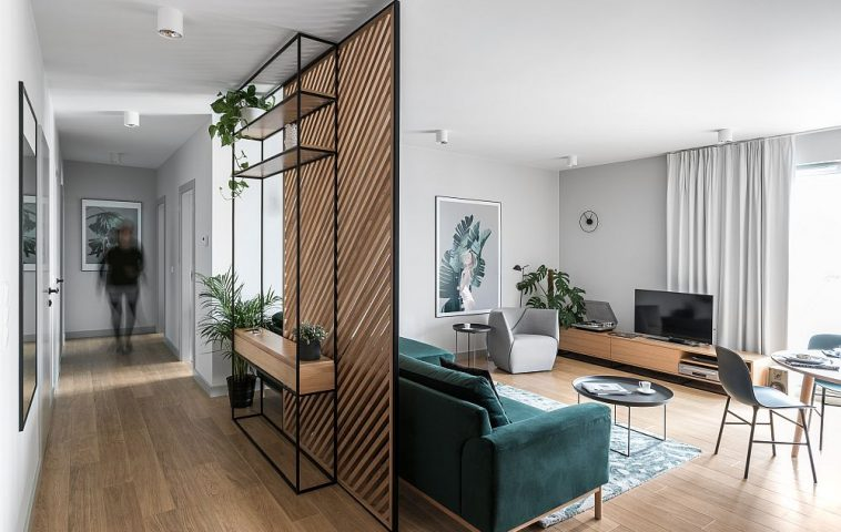 Pentru a separa livingul față de hol, arhitecții au prevăzut un panoul dintr-o structură metalică și riflaje din lemn. În spatele panoului o mică masă consolă e locul pentru chei și scrisori, atunci când proprietari ajung acasă.
