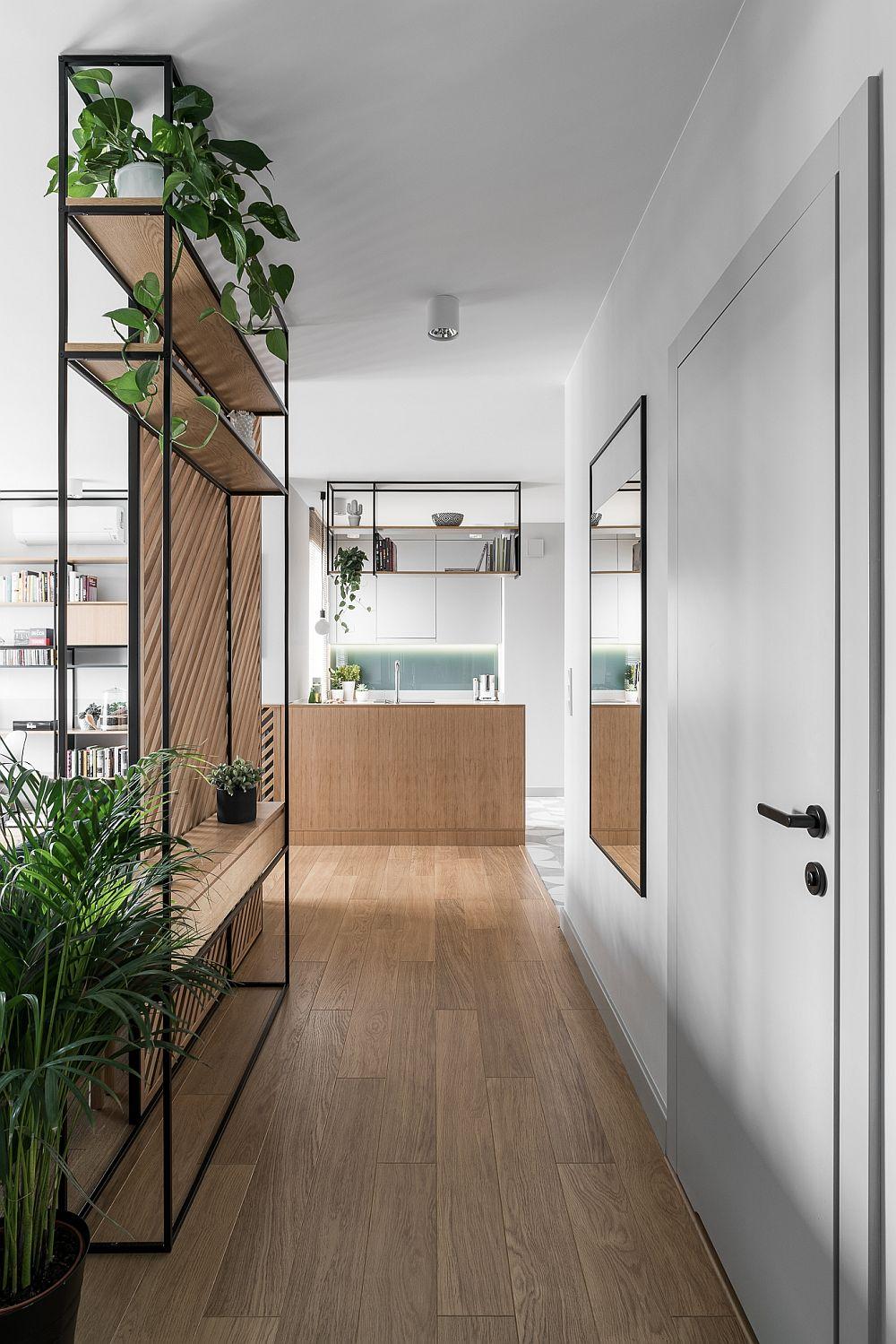 Dinspre dormitoare, culoarul holului este clar conturat prin panoul ce separă livingul și direcționează privirea către zona bucătăriei. Fiind practic în același spațiu, aceste piese de mobilier și separare sunt gîndite în relație unele cu altele, cum se vede și în imagine rafturile de sus din spatele canapelei concepute la același nivel cu raftul de deasupra chiuvetei din bucătărie.
